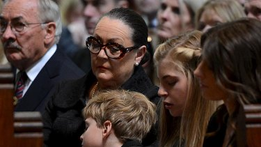 Jim Stynes' family, including son Tiernan, left, daughter Matisse and widow Sam listen to the service.