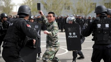 A participant playing the role of an attacker faces riot police during a security drill in Urumqi, Xinjiang.