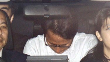 Under arrest … former Aum Supreme Truth cult member Katsuya Takahashi, centre, is driven to a Tokyo police station.