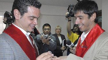 Alex Freyre, right, receives a wedding ring from his partner Jose Maria Di Bello.
