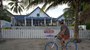 A man rides a bicycle past the beachside entrance to the home of software company founder John McAfee in Ambergris Caye, Belize.