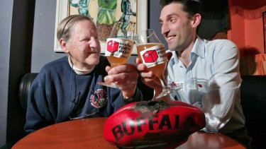Keith Dunstan and grandson Jack Dunstan toast a burnt football in 2008.