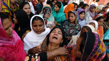 People try to comfort a Pakistani Christian mother during the funeral of her two daughters, killed in a suicide bombing by a Pakistan Taliban faction in Lahore in March.