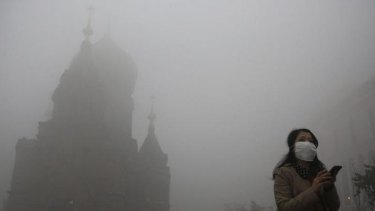 A haze descends: a woman wears a mask to endure the smog in Heilongjiang province.