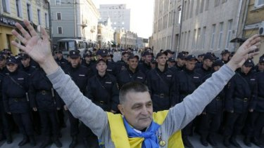 A man with a Ukrainian flag on his shoulders stands near a riot police line standing guard during an anti-war rally in Moscow, September 21, 2014.