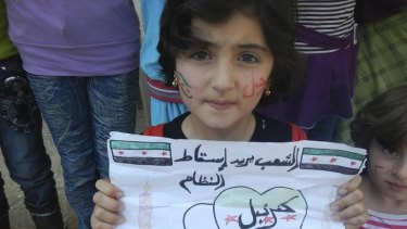 A girl in Kafranbel, near the town of Idlib. Her sign reads 'the people want the fall of the regime'.