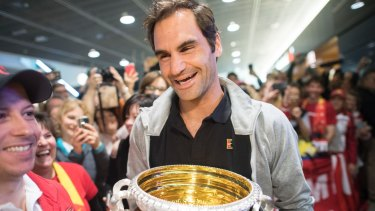 All smiles: Roger Federer lands in Zurich with the Australian Open trophy.