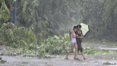 Residents hold an umbrella as they walk on a street in front of fallen tree branches during heavy rainfall under the influence of Typhoon Kalmaegi in Qionghai, Hainan province.