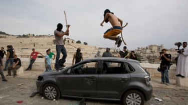 Palestinian youths destroy a car outside Jerusalem's Old City this week after a day of clashes with Israeli forces.