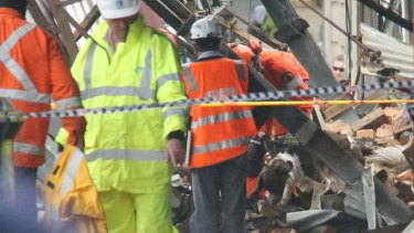 A sniffer dog searches the site of the building explosion in Darling Street, Rozelle.