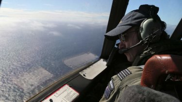 Royal New Zealand Air Force P-3 Orion's captain, Wing Commander Rob Shearer watches out of the window of his aircraft while searching for the missing Malaysia Airlines Flight MH370 in the southern Indian Ocean.