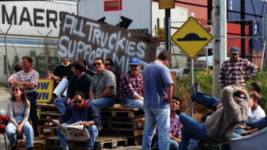 "Picketers sit in front of a sign which reads ""All Truckies Support MUA"" at Swanson Dock, Melbourne. April 18, 1998."
