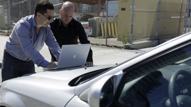 Security consultants Don Bailey, left, and Mathew Solnik, right, with iSEC Partners, demonstrate with a computer how they force cars with certain alarm systems to unlock their doors and start their engines by sending them text messages.