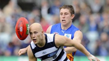 Cats wizard Gary Ablett, with Brisbane's James Polkinghorne in tow, loses sight of the ball.