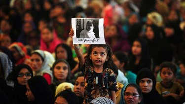 A child holds aloft a photo of Malala Yousafzai during a protest in Karachi over her shooting by the Taliban.