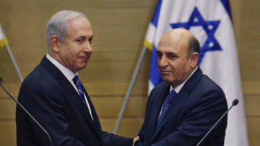 Political lifeline ... Israel's Prime Minister Benjamin Netanyahu, left, and Kadima party leader, Shaul Mofaz, shake hands before holding a joint press conference announcing the new coalition government in Jerusalem.