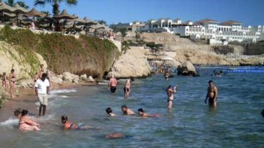Tourists take a dip in the sea at a beach that is excluded from a swimming ban at the Red Sea resort of Sharm el-Sheikh.