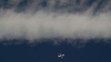 An airliner flies under smoke left by a Ukrainian military plane a few kilometres from the Russian border on July 16.