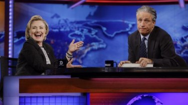 Former U.S. Secretary of State Hillary Rodham Clinton reacts to host Jon Stewart during a taping of The Daily Show with Jon Stewart in New York.