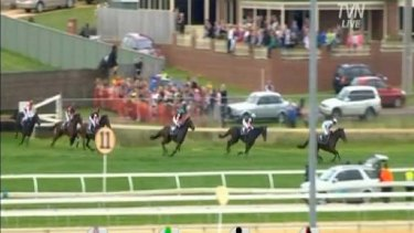 Riderless Banna Strand jumps into the crowd, top left.