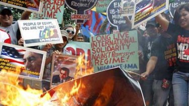 Demonstrators burn a replica of the US flag and a picture of Hosni Mubarak outside the US embassy in Manila.