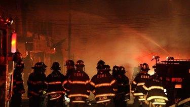 Fiery blaze ... New York City firefighters try to bring growing flames under control on Rockaway Beach Boulevard in Queens.