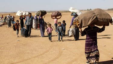 Newly arrived Syrian Kurdish refugees walk with their belongings after crossing into Turkey from the Syrian border town of Kobane on Tuesday.