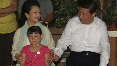 Wooing their hosts: China's President Xi Jinping and his wife Peng Liyuan sit next to a child during their visit to a family at a coffee farm in Costa Rica.
