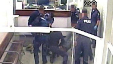 A CCTV image showing police crowding around the man who was Tasered multiple times.
