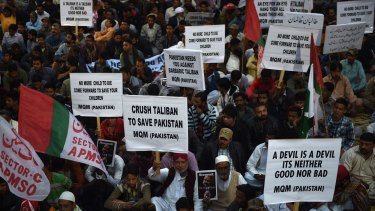 Activists  of Muttahida Qaumi Movement (MQM) party hold anti-Taliban placards in a protest rally in Karachi on Friday.