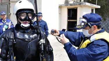 Check please ... a frogman is scanned for radiation after interrupting an undersea search at the port of Obama in north-eastern Japan.