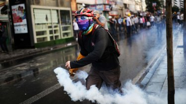 A protester throws back a tear gas canister at riot police during clashes in the streets near Taksim square.