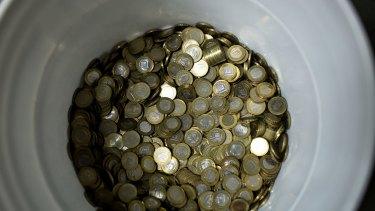 A bucket of bolivar coins in a market in Caracas.