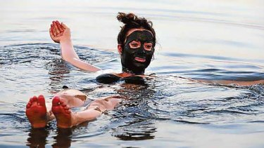 A tourist, her face covered with mud, floats near the Dead Sea resort of Kalia.