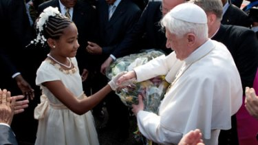 Sticking to Catholic doctrine...Pope Benedict XVI is greeted by a girl on his arrival at Yaounde on a six-day visit to Africa.