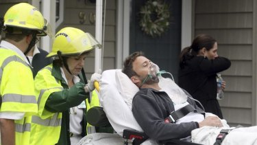 A man is taken away by paramedics at the scene of the crash.