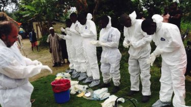 Volunteers prepare to remove the bodies of people who were suspected of contracting Ebola and died in the community in the village of Pendebu, north of Kenema, in Sierra Leone.