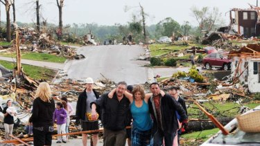 Residents of Joplin, Missouri, help a woman who survived in her basement after a tornado hit the city on Sunday. Photo: AP