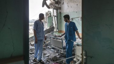 Staff members of a Deir al-Balah hospital look over the damage caused by Israeli shelling.