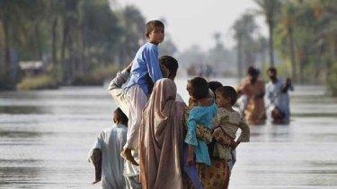 A Pakistani family makes their way through flooded streets in Muzaffargarh near Multan, Pakistan. <i>Picture: AP</i>