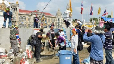 Anti-government protesters mix concrete in an attempt to build a wall in front of the gate of the Government House in Bangkok on February 17, 2014.