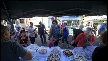 Locals and visitors at the Frangipani Gluten Free stall at Talbot local market . The stall is run by Fran, who has been coming to the market for 8 years.