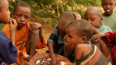 Relief ... Ali Hassan, in orange, and other children eat their first meal in days.