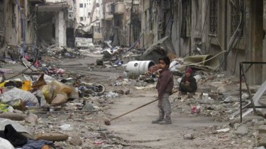 A child clears damage and debris in the besieged area of Homs.