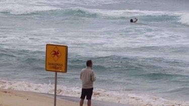 Subtle killer: A swimmer at Bondi swims near a rip tide despite lifeguard warning signs.