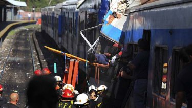 Crumbled wreckage ... Firemen rescue wounded passengers from the commuter train.