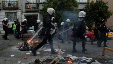 Protest: Police walk past burning debris in the Cihangir district of Istanbul.