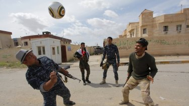 Members of the Iraqi security forces play football in Tikrit after taking it from Islamic State.