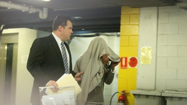 The man charged with attempted  murder  is led away at Merrylands police  station today.