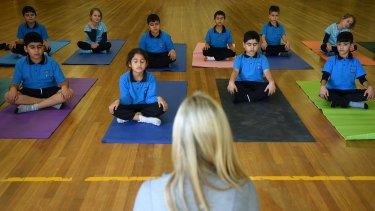And ... exhale: Danielle Begg conducts a yoga class at Liverpool West Public School.